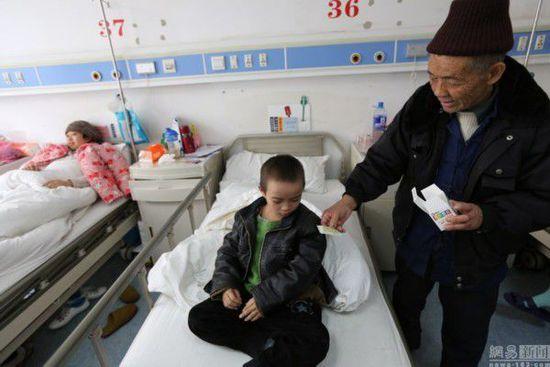 """2014年1月1日13点09分,手拿药片的卢朝礼对着孙子好言相劝,让孙子赶紧把药片吃了:""""这次住院,医院确诊孙娃子得的是淋巴瘤。当天是元旦,医院的医生都休息了,只有护士值班。由于放假前孙娃子又感冒发高烧了,医生开了一堆药片和十来瓶吊水,必须要在这几天放假的时间内把药吃完,把吊水打完,把感冒治好。医生说了,等放假结束后,孙娃子如果感冒好了,再继续15天左右的放疗。(注,诊断证明书上确诊为:霍奇金淋巴瘤,是恶性肿瘤。)"""
